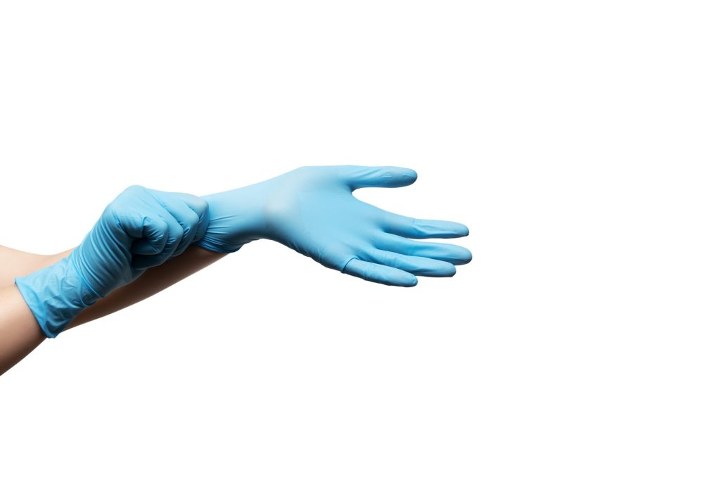 Plumber putting on a pair of blue gloves