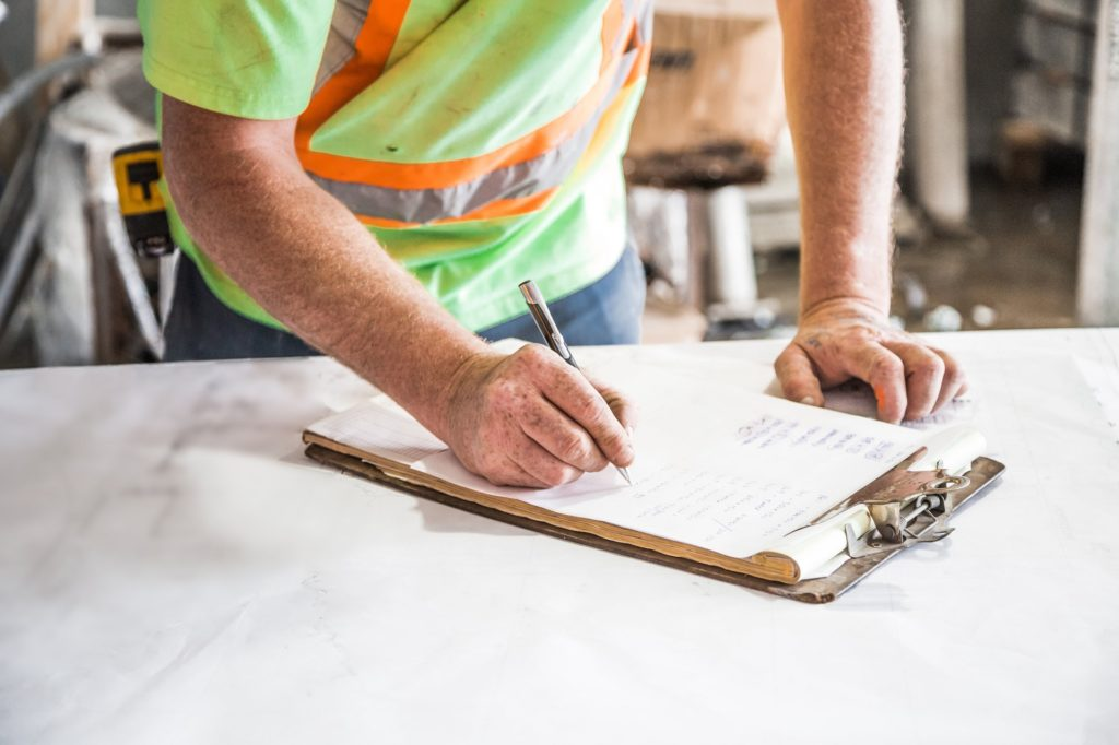 Inspector writing on a clipboard during a commercial plumbing inspection
